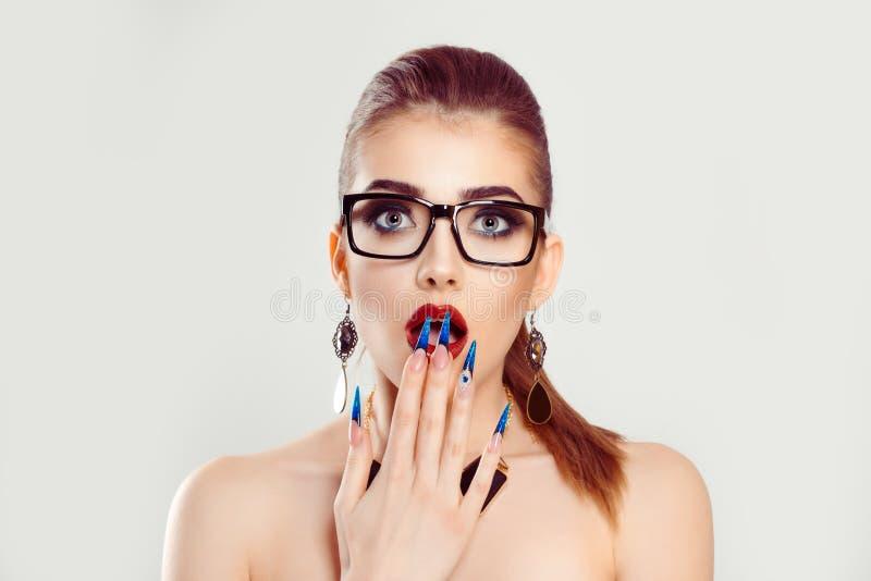 戴眼镜的震惊妇女与开放嘴覆盖物用震惊的手 库存图片