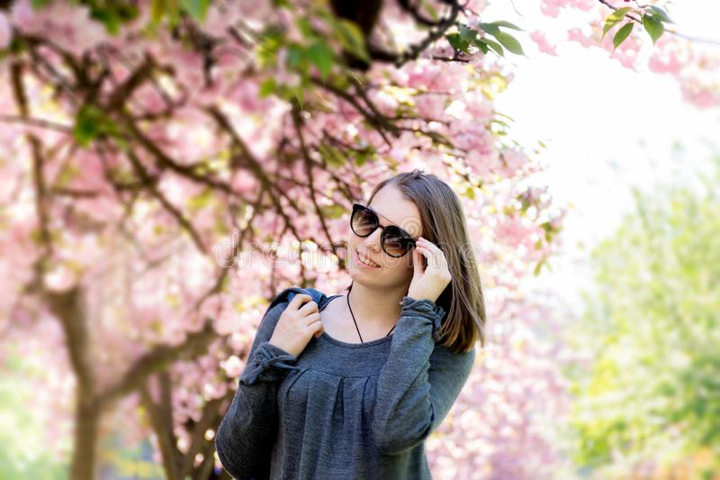 戴眼镜的青少年的女孩以开花的佐仓为背景 免版税库存照片