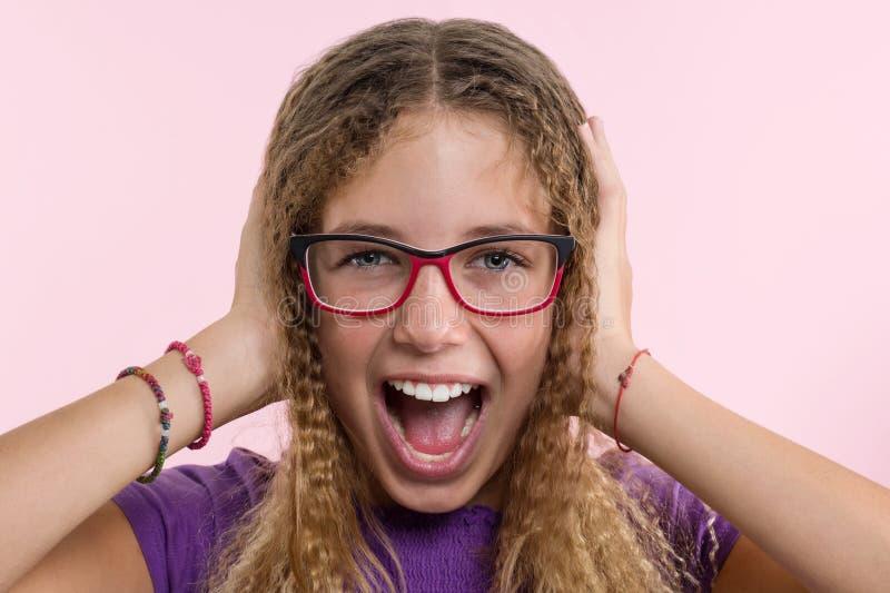 戴眼镜的青少年的女孩,与长的头发抓她的头并且是情感的困惑 背景桃红色工作室 免版税库存照片