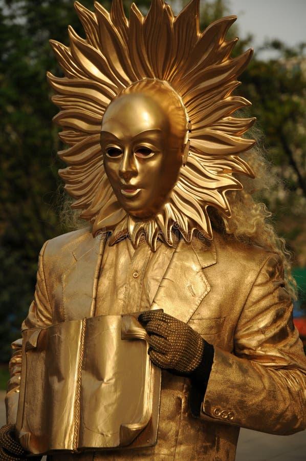 戴着一个金黄面具的街道艺术家 免版税库存照片