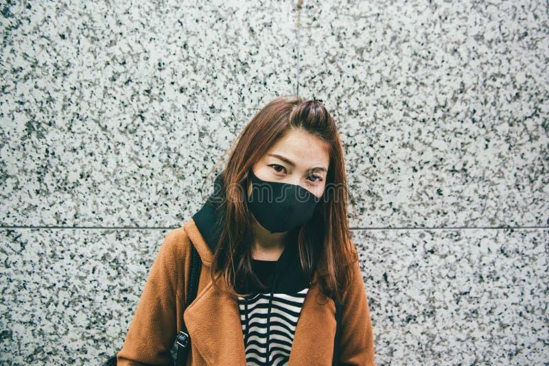 戴着一个黑嘴面具的年轻亚裔妇女作为她遭受严厉大气污染 库存照片