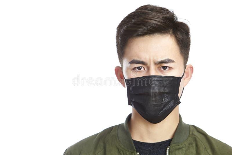 戴着一个黑面具的年轻亚裔人 库存照片