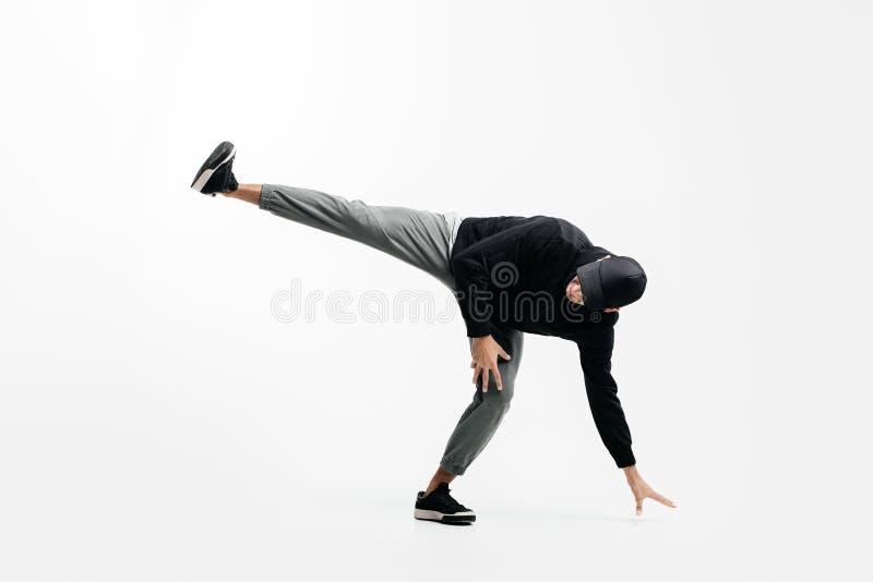 戴着一条黑运动衫、灰色裤子和帽子的英俊的年轻人跳舞breakdance 免版税图库摄影