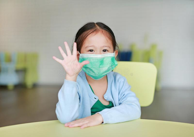 戴着与陈列五手指的小亚裔儿童女孩一个防毒面具坐孩子椅子在儿童居室 库存照片