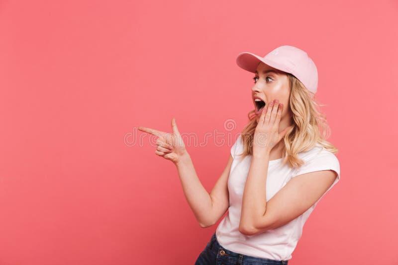 戴着偶然T恤杉和帽子的时髦白肤金发的妇女20s画象指向手指在旁边copyspace 免版税库存照片