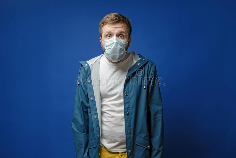 戴着医用口罩的震惊的人,睁大了眼睛,吓得目瞪口呆 病毒传播的概念 图库摄影