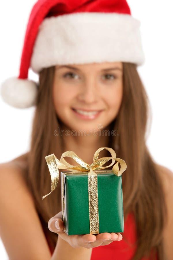 戴着圣诞老人帽子的年轻微笑的圣诞节妇女给礼物 免版税库存照片