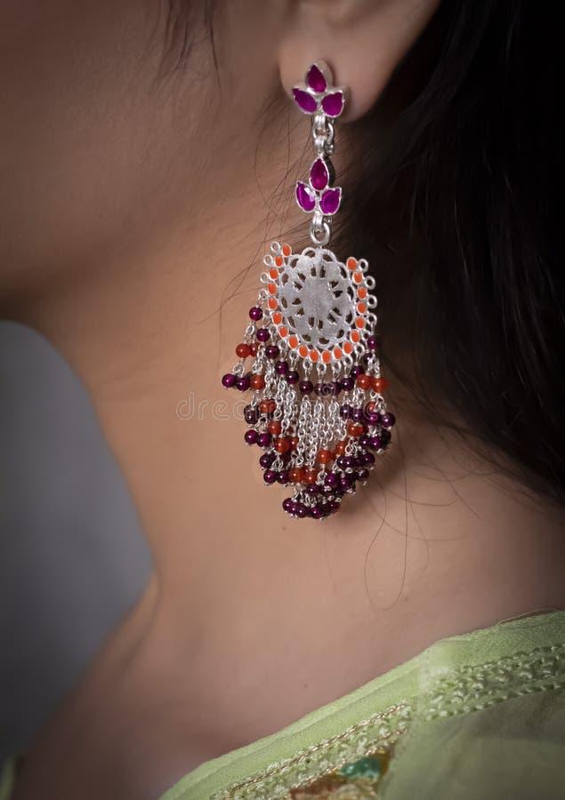 戴着在耳朵的妇女红色耳环 库存图片