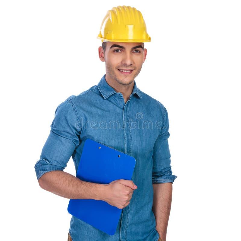 戴着坚硬帽子和拿着纸的轻松的工程师画象 库存图片