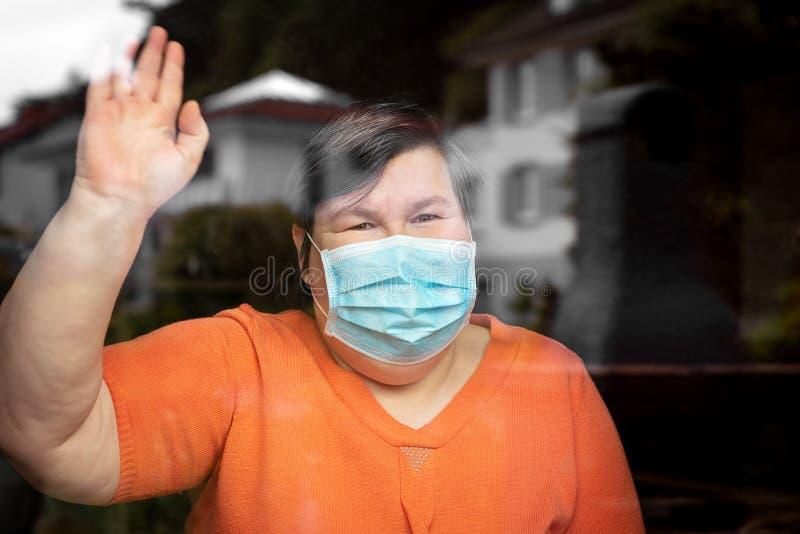 戴着手术面罩的精神残疾妇女向窗外挥手致意, 库存照片