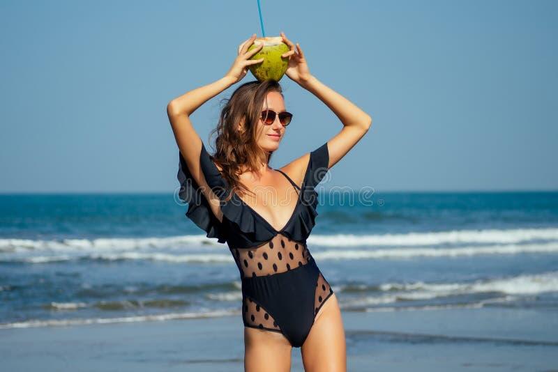 戴着时髦一件式黑色泳装太阳镜、棕褐色美女站在沙滩上,手里拿着椰子 免版税图库摄影