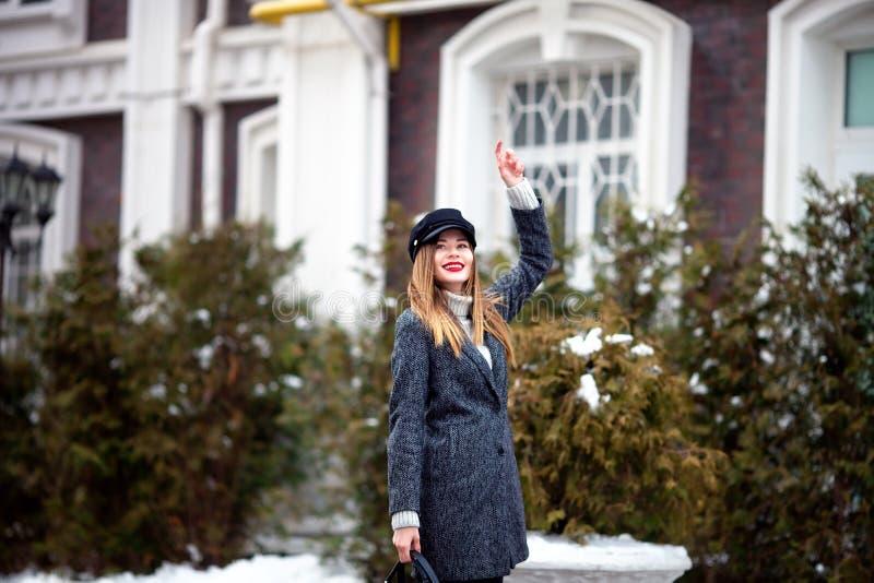 戴着时髦帽子的年轻美丽的时髦的女人室外画象  时髦的衣裳和辅助部件 式样走在街道 免版税库存照片