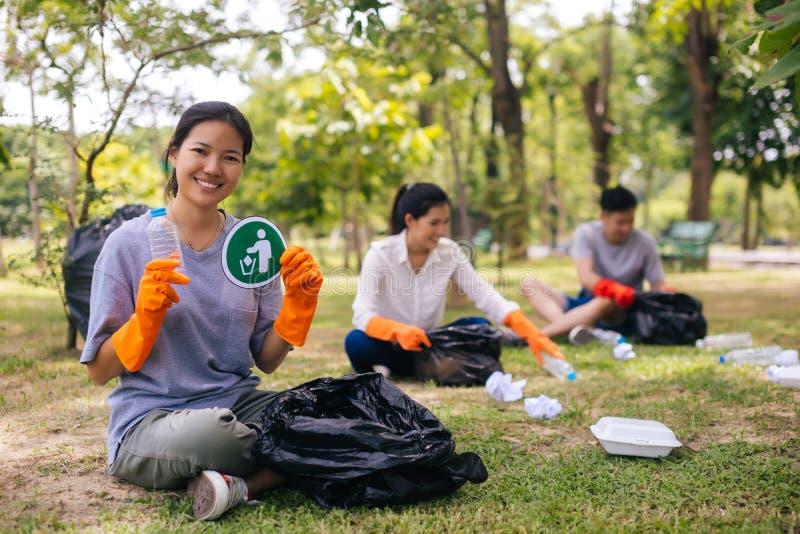 戴着橙色手套和收集在垃圾桶袋子的年轻亚洲妇女和小组志愿者垃圾在公园 图库摄影