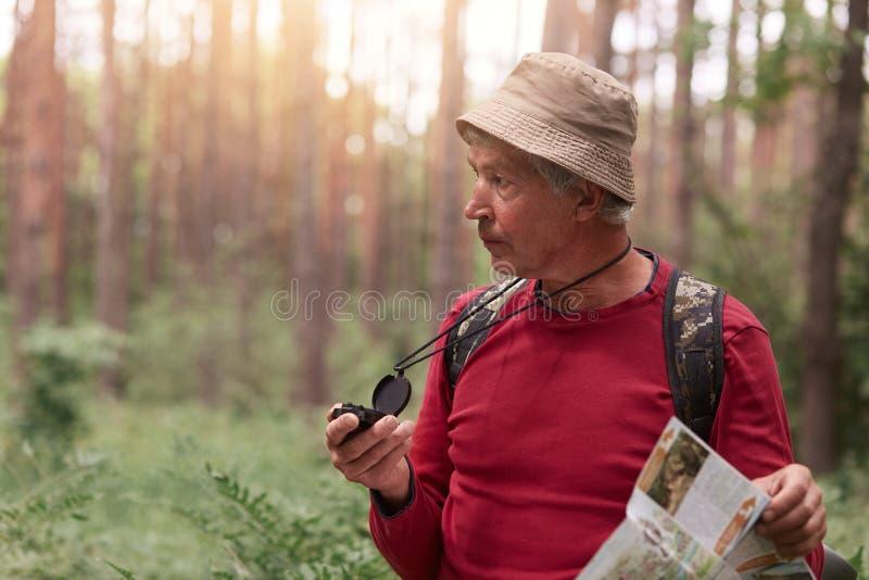 戴着红色偶然毛线衣和帽子的徒步旅行者,摆在与背包,搜寻与指南针的正确的方向,丢失在森林里,点燃了 库存照片