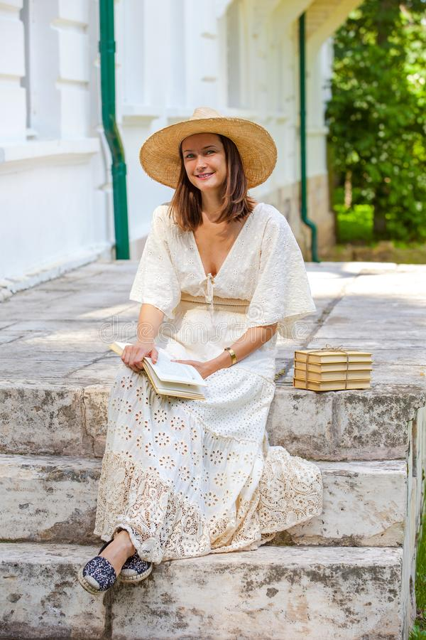 戴着草帽、手拿书的美丽微笑女人 免版税库存照片