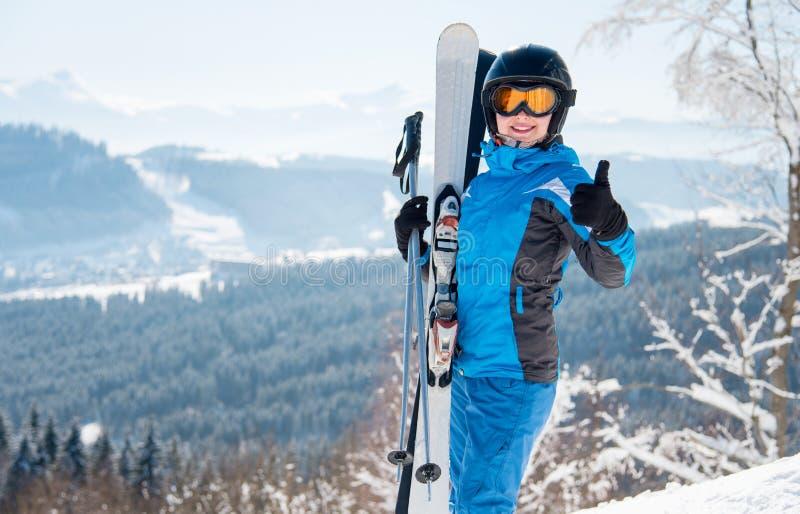戴着蓝色滑雪服、黑盔甲和面具的愉快的女性滑雪者微笑显示摆在的赞许在山 免版税图库摄影