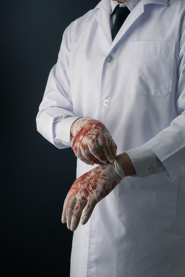 戴着血淋淋的乳汁手套的白色外套的一位医生 库存图片