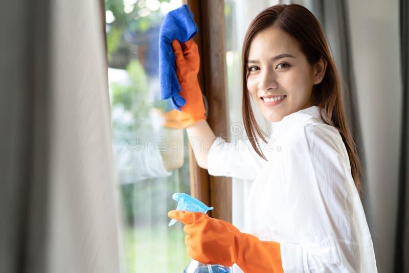 戴着防护手套的美丽的年轻亚裔妇女清洗窗口由喷洒的清洁产品和抹与海绵 妇女 库存照片