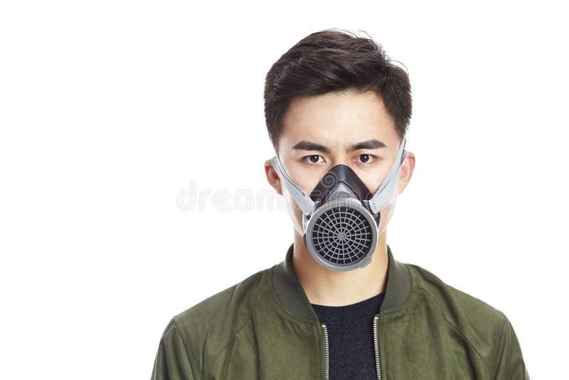戴着防毒面具的年轻亚裔人 免版税库存图片