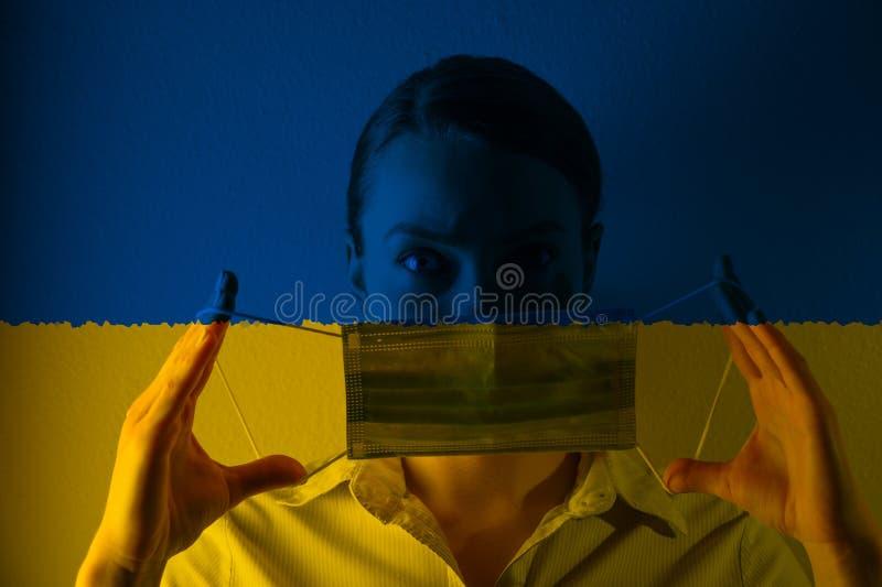 戴着面具的乌克兰国旗背景女孩;疾病危险,新病毒 免版税图库摄影