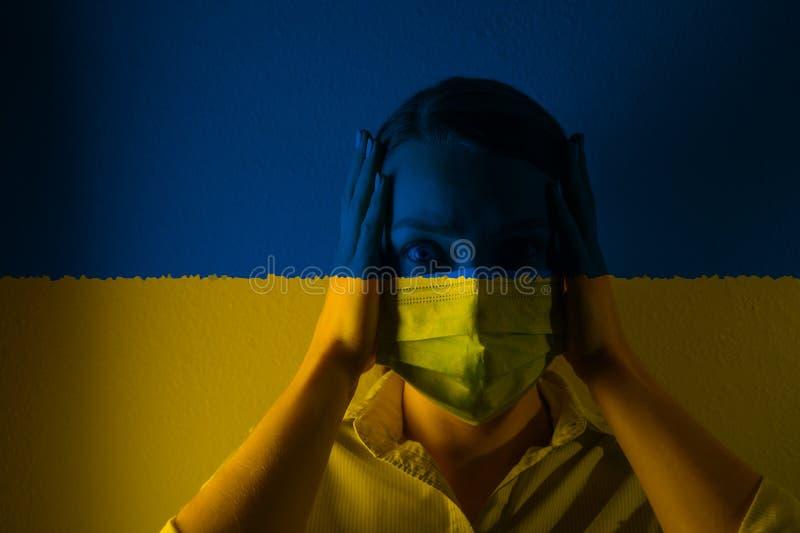 戴着面具的女孩,在乌克兰国旗的背景下,危险和威胁,病毒的爆发 照片 库存图片