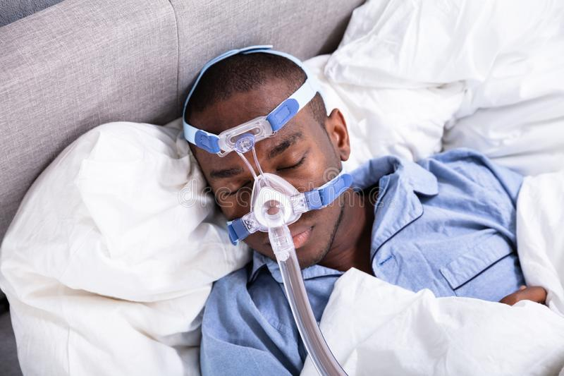 戴着CPAP面具的人睡觉在床上 免版税库存图片