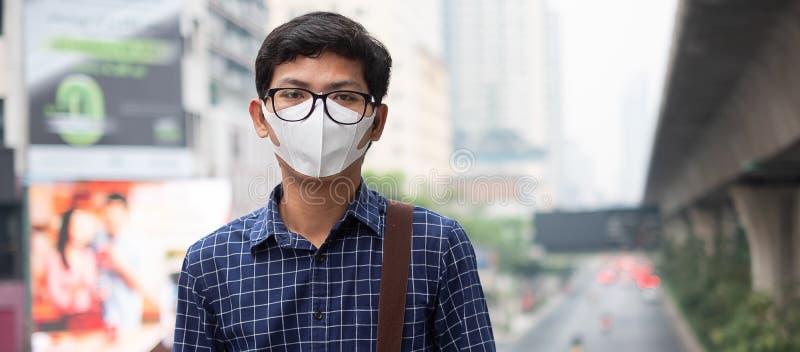 戴着N95呼吸面具的年轻亚裔人保护和过滤pm2 5反对交通和尘土城市的粒状物质 免版税库存图片