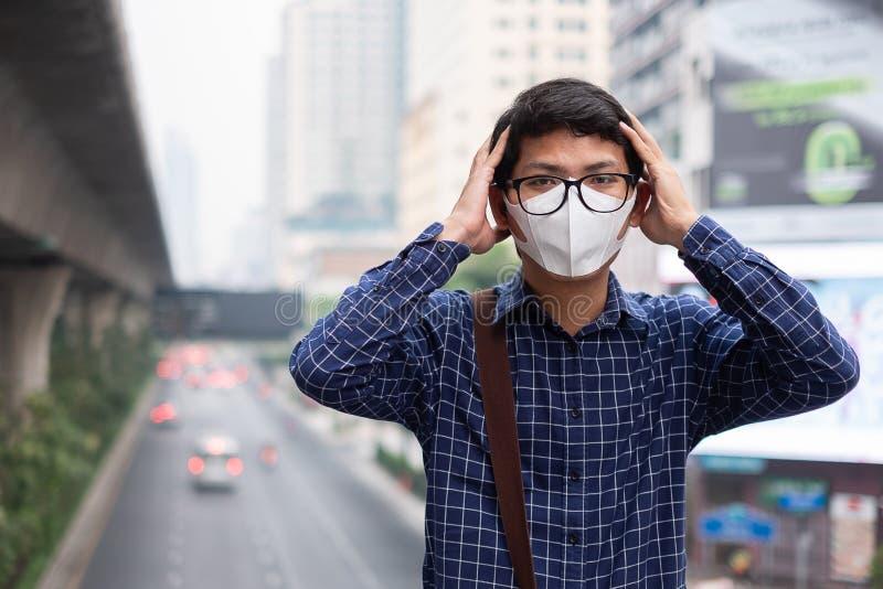 戴着N95呼吸面具的年轻亚裔人保护和过滤pm2 5反对交通和尘土城市的粒状物质 免版税库存照片