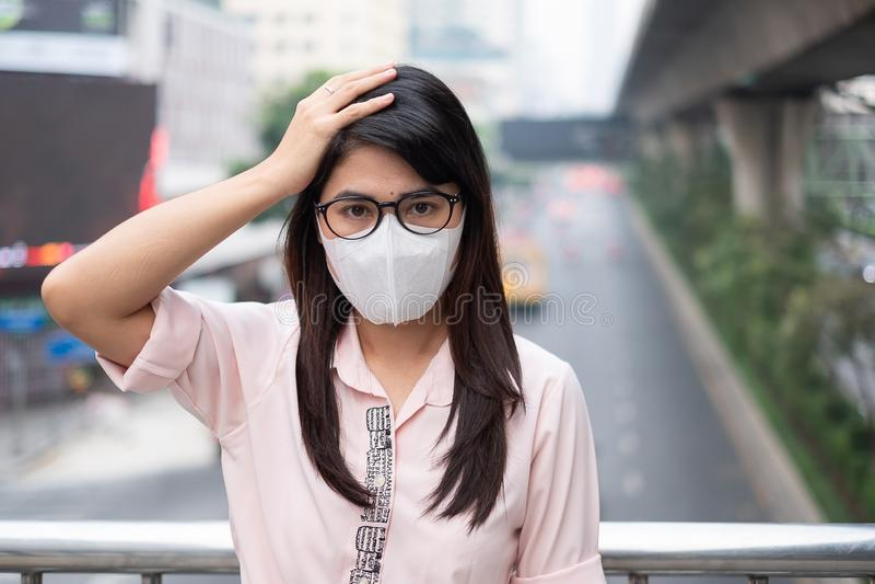 戴着N95呼吸面具的年轻亚裔妇女保护和过滤pm2 5反对交通和尘土城市的粒状物质 库存图片