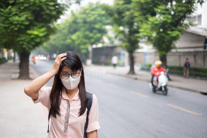 戴着N95呼吸面具的年轻亚裔妇女保护和过滤pm2 5反对交通和尘土城市的粒状物质 免版税库存图片