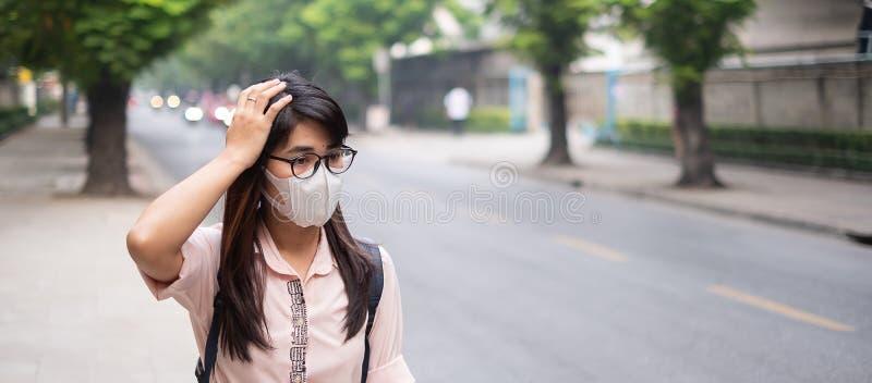 戴着N95呼吸面具的年轻亚裔妇女保护和过滤pm2 5反对交通和尘土城市的粒状物质 图库摄影