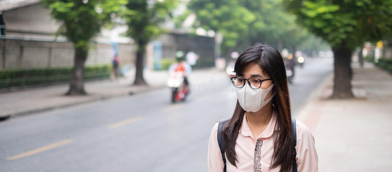 戴着N95呼吸面具的年轻亚裔妇女保护和过滤pm2 5反对交通和尘土城市的粒状物质 库存照片