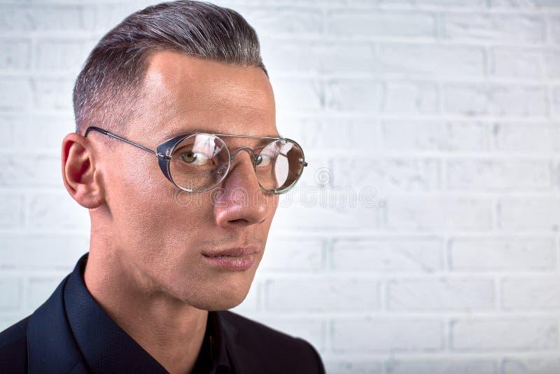 戴站立在砖墙背景的眼镜的特写镜头画象年轻英俊的商人 免版税库存照片