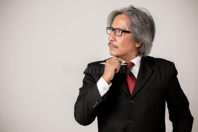 戴站立w的白发佩带的髭眼镜的高级职员 免版税库存图片
