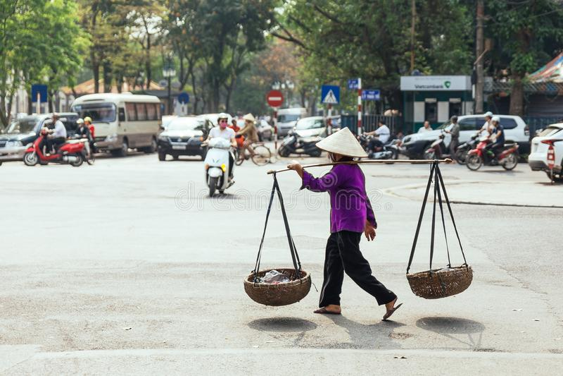 戴紫色布料和圆锥形帽子的妇女 运载与里面材料的篮子与在街道上的一根运载的杆在河内,越南 库存照片