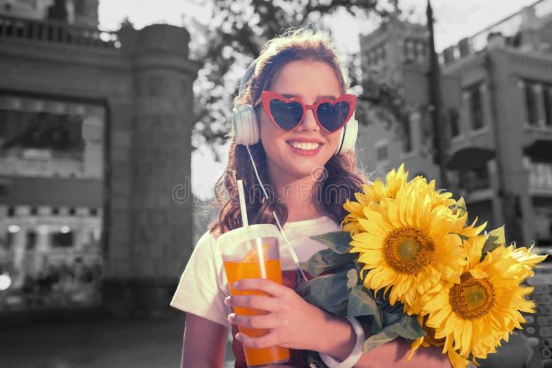 戴红色太阳镜的微笑的妇女拿着向日葵和杯汁液 免版税图库摄影