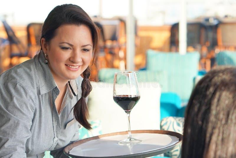 戴红酒眼镜的女服务员  免版税库存照片