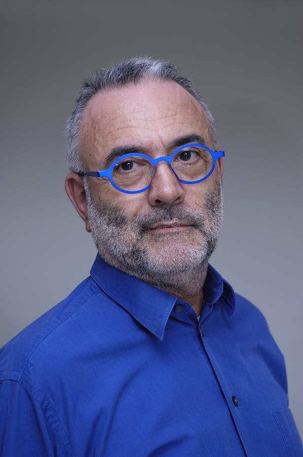 戴蓝色衬衣和眼镜的人 免版税图库摄影