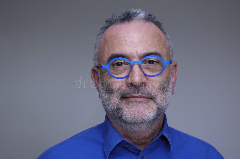 戴蓝色衬衣和眼镜的人 免版税库存照片
