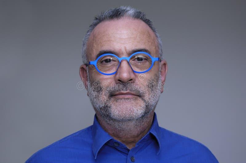 戴蓝色衬衣和眼镜的人 免版税库存图片