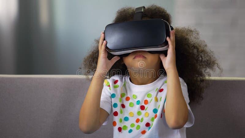 戴虚拟现实眼镜和打比赛的可爱的黑人女孩,休息 图库摄影