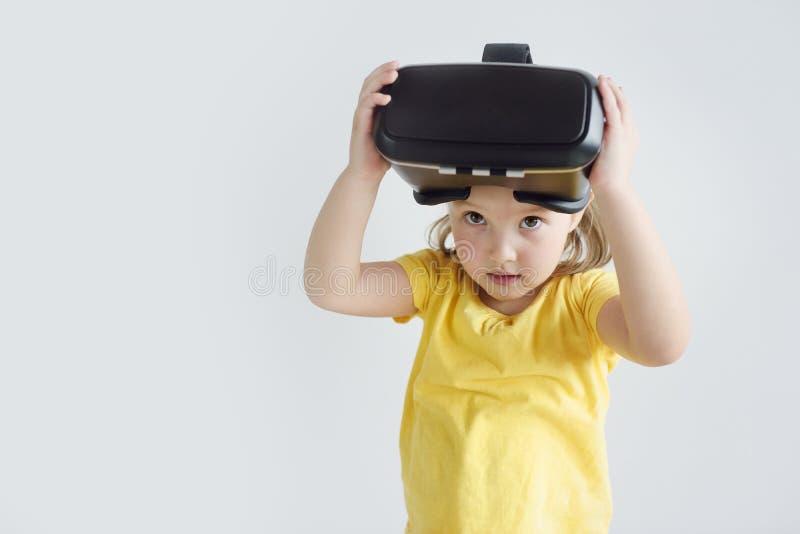戴虚拟现实眼镜的一女孩 佩带虚拟现实风镜电影或演奏录影的孩子 库存图片