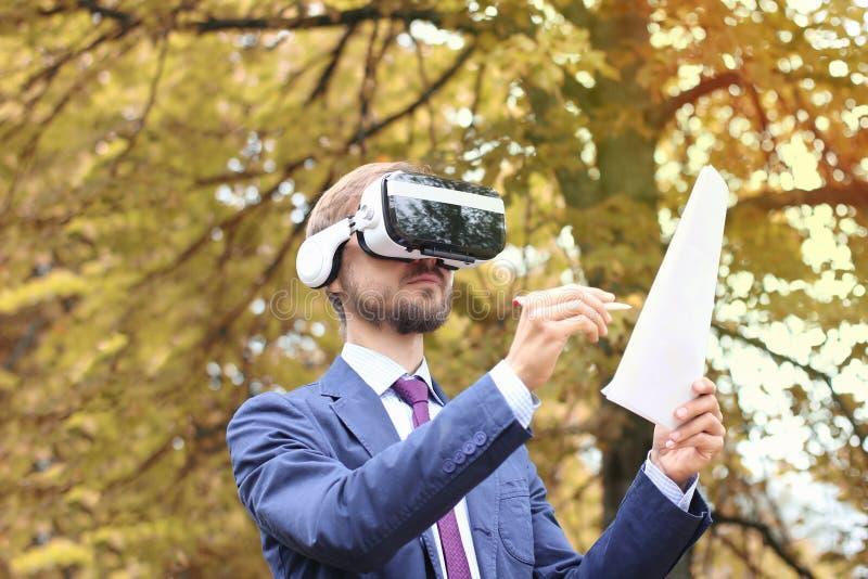 戴虚拟现实眼镜的愉快的有胡子的商人在秋天公园签署文件 电子署名,未来技术或者 库存图片