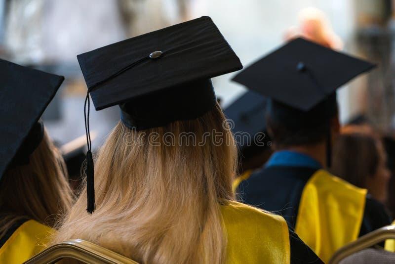 戴褂子和帽子的学生坐户内,等待对rece 库存图片