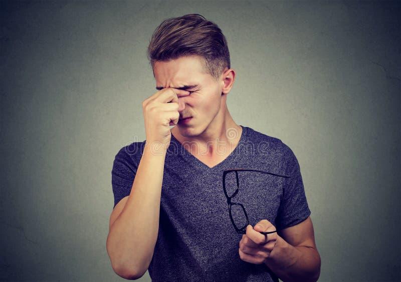 戴遭受累眼的眼镜的年轻人 免版税库存照片