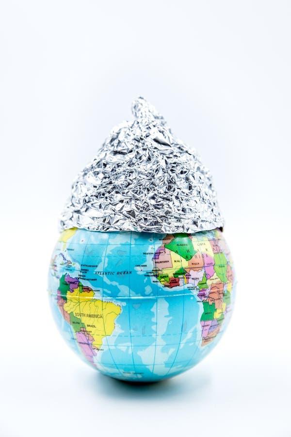 戴锡箔帽的地球仪,在白色背景中被孤立,概念阴谋论 免版税图库摄影