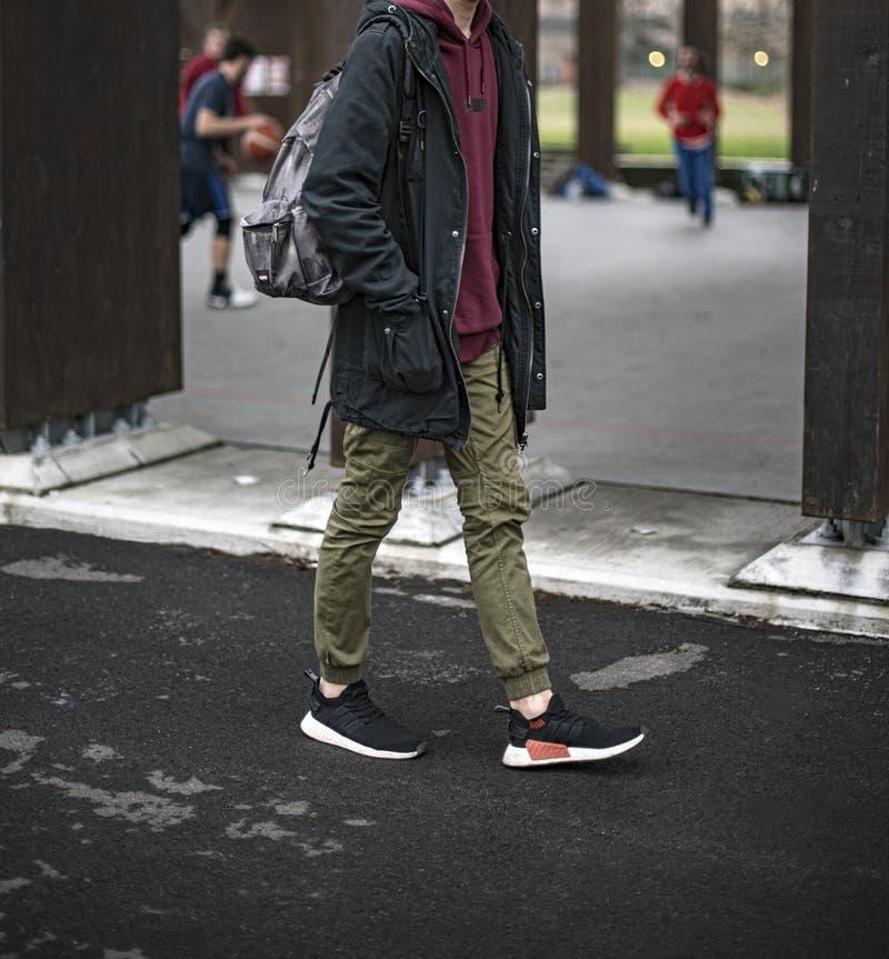 戴阿迪达斯NMD 2鞋的年轻人 免版税库存照片