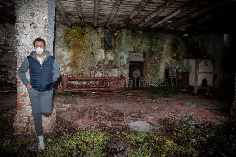 戴面具的男人,倚在一列废弃的废墟上,象征着悲伤、绝望和对疾病的恐惧 库存照片