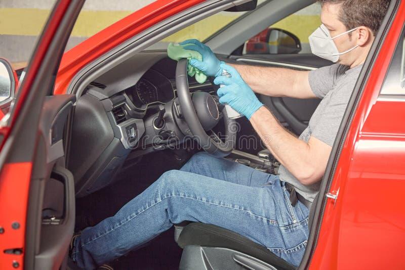 戴面罩和橡胶手套消毒车的人 库存照片