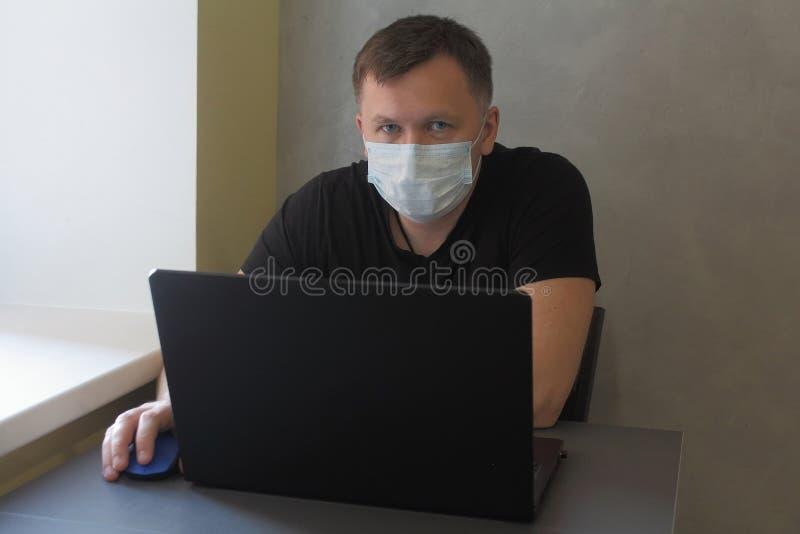 戴面罩的男子因检疫冠状病毒covid-19大流行而在家工作 带笔记本电脑的商务人员在家远程工作 免版税图库摄影
